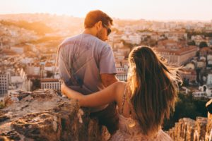 woman with arm around couple overlooking city
