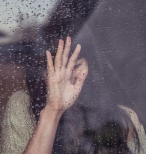 woman crying in the window in the rain