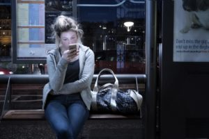 woman with phone on train at night texting