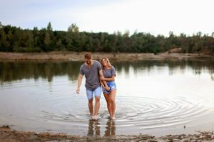 couple wading in a lake