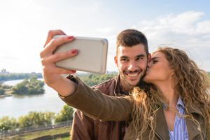 kissing couple taking selfie