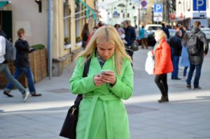 woman in coat looking at phone