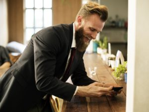 man with beard laughing with phone