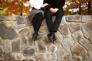couple sitting on a stone wall in the autumn