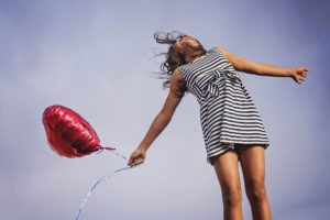 woman in dress with heart balloon
