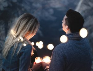 couple holding candles at night