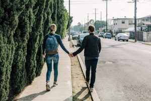 couple walking on the sidewalk and the curb