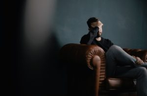 frustrated man sitting on couch