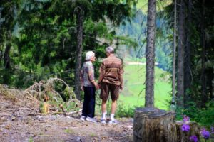 older couple holding hands in the woods