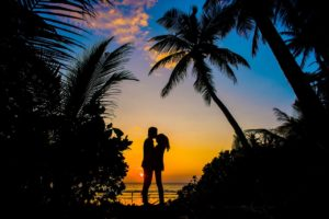 silhouette of a man and woman kissing at the beach