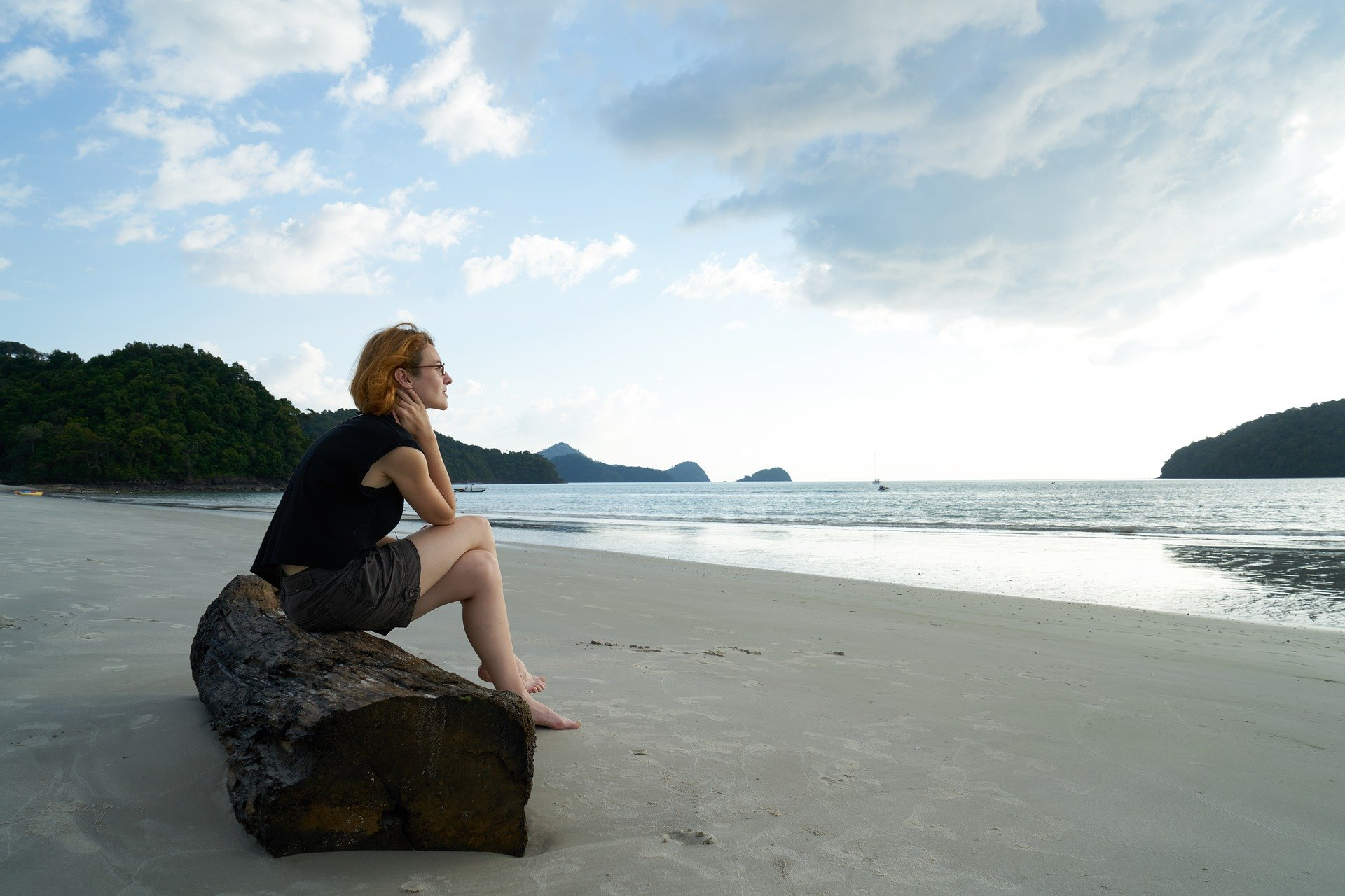 lonely woman sitting on a rock looking at water